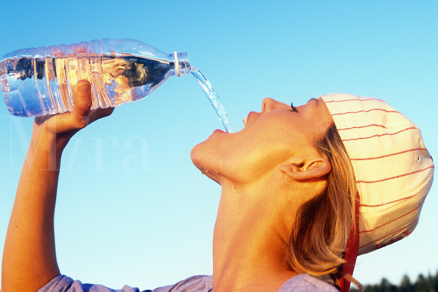 thirsty young woman drinking bottled water.