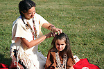 Native American Indian woman combing hair of young child with fingers