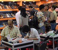 Businessman strike a deal at a the stall of a shoe manufacturer at the 101st Guangzhou International Trade Fair (a.k.a the China Import and Export Fair) in Guangzhou, China. The fair attracts tens of thousands of Chinese manufacturers and foreign businessmen and buyers from all around the world whom are using China as a manufacturing and sourcing base..17 Apr 2007