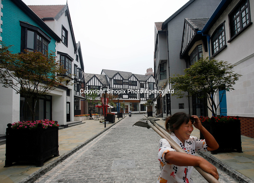 """A woman carrying her tools walks through a street at Thames Town, in Shanghai, China. Thames Town is one of several satellite townships that Shanghai is building in hopes of luring residents away from the city centre, and claims to allow people to """"taste authentic British style of small town""""..21 Jul 2006"""