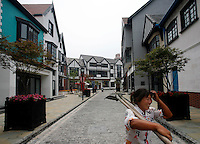 "A woman carrying her tools walks through a street at Thames Town, in Shanghai, China. Thames Town is one of several satellite townships that Shanghai is building in hopes of luring residents away from the city centre, and claims to allow people to ""taste authentic British style of small town""..21 Jul 2006"