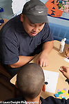 Preschool 3-4 year old male visiting teacher in training  working with boy on art activity vertical