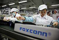 Employees work on the assembly line at Hon Hai Group's Foxconn plant in Shenzhen, China. Hon Hai is the parts supplier for many hi-tech companies around the world including Apple Inc., Hewlett-Packard Co. and Dell Inc. There have been 12 suicides at the company's 300 thousand employee strong factory complex in Shenzhen so far this year..26 May 2010