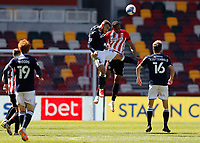 17th April 2021; Brentford Community Stadium, London, England; English Football League Championship Football, Brentford FC versus Millwall; Mason Bennett of Millwall heads the ball above the challenge from Ethan Pinnock of Brentford
