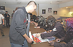Signing autographs for contest winners.
