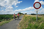 Belgium, West Vlaanderen, near Ypres: Cyclists on cycle path through Belgian countryside.