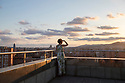 Spain - Barcelona - A young woman watches the sun rise over Barcelona.