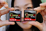 SanDisk employee Tanya Chuang holds up two of SanDisk's new large 16 and 12 GB compact flash cards at company headquarters in Milpitas, Calif., Thursday, Oct. 19, 2006. (AP Photo/Paul Sakuma)
