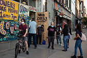 New York New York<br /> June 6, 2020<br /> <br /> After several nights of looting, nearly all ground level windows in Soho are covered with plywood. Most of the shops had been looted others are boarded for protection. <br /> <br /> At curfew hours - 8pm till 5am police cordon of certain streets and only allow residence with an ID to pass.<br /> <br /> On other streets people came out and congregate for the first time in months as both curfew and coronavirus quarantine would be lifted within a day.