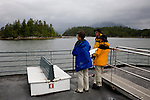 Passengers view the Broken Islands, Barkley Sound, seen in rain from the deck of a pocket frieghter, penetrates Vancouver Island's west coast from the Pacific Ocean. The popular fishing and kayaking Broken Islands group protect the entrance.