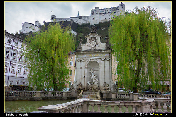 Salzburg, Austria.<br /> These clouds and white buildings make for tough photography. Here, I minimized the boring sky and I found some trees in spring foliage for some much needed color. The foreground railing acts as a frame.