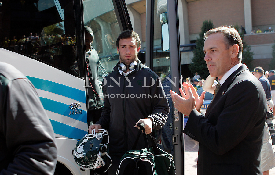 Michigan State head coach Mark Dantonio, right, cheers on his players getting off the bus at Michigan Stadium before an NCAA college football game with Michigan, Saturday, Oct. 9, 2010, in Ann Arbor, Mich. Dantonio is planning to watch the game from the press box, still recovering from his heart attack on Sept. 25, 2010. (AP Photo/Tony Ding)