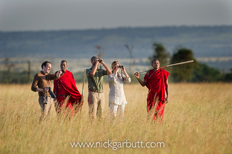 Tourists and guide with Masaai warriors wearing red shukas watching wildlife. Walking safari across the open grassland of the Serengeti National Park, Tanzania.