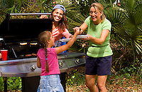 Family and friends having picnic with mixed ethnic people having hamburgers and laughing outdoors at home