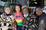 An adult daughter and son pose with their parents in traditional African costume in front of their African gift shop in the Leimert Park neighbrohood of Los Angeles, CA