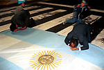 """A Christian demonstration to """"save Argentina"""" in Plaza de Mayo. Two men pray onto a Argentine flag. 2000s 2002"""