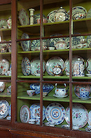 Detail of a collection of china displayed in a long cabinet in one of the corridors