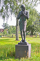 A statue of Carl Linnaeus holding a bird by Gerda Sprinchorn standing in the church yard of Stenbrohult with Linnaeus father was priest. Smaland region. Sweden, Europe.