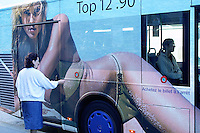 Switzerland. Ticino. Cassarate. An old woman will enter a public city bus, covered with a huge advertsing for a summer swimming costume. A young woman is seated inside in the bus. Cassarate is just outside Lugano. 21.05.03 © 2003 Didier Ruef