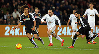 Leon Britton of Swansea (C) charges forward against Valon Behrami (L) and Miguel Britos of Watford (R) during the Barclays Premier League match between Swansea City and Watford at the Liberty Stadium, Swansea on January 18 2016