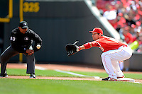 Cincinnati Reds first baseman Joey Votto #19 takes a throw as umpire Adrian Johnson #80 looks on to make the call during a game against the Miami Marlins at Great American Ball Park on April 20, 2013 in Cincinnati, Ohio.  Cincinnati defeated Miami 3-2 in 13 innings.  (Mike Janes/Four Seam Images)