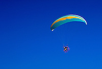 A Powered Parachute (Atlas canopy) with pilot, airborne in a wide, blue sky. Arizona.