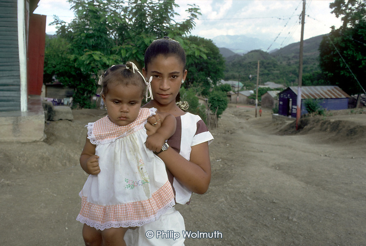 DOMINICAN REPUBLIC<br /> Young girl with her baby sister in the coffee-growing mountain village of Arroyo Cano