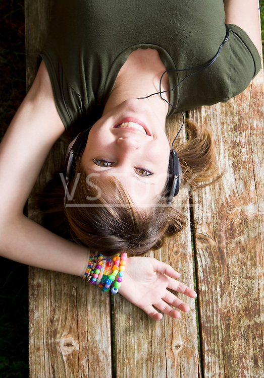 USA California, Fairfax, teenage girl (16-17) lying on wooden bench and listening music