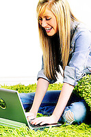 Beautiful blonde teen sitting on a shag rug using a laptop computer.