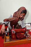 Dehradun, India.  Indian Muslim Woman Working with Manual Sewing Machine in Sewing Instruction Class.