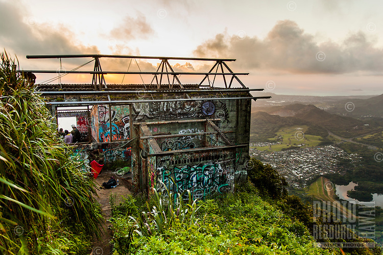 """Dawn light on an abandoned U.S. military building covered in graffiti near the top of Ha'iku Stairs (or """"Stairway to Heaven"""") hiking trail in Kane'ohe, O'ahu."""