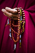 A Buddhist monk meditates while turning the beads outside the Ramtanka Temple in Paro, Bhutan. Photo: Sanjit Das/Panos