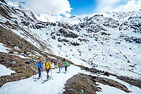 The Ortler Group in northern Italy is a popular region for spring ski touring using the huts for overnights to ski all the many peaks in the mountain group. A group of skiers arriving at the Rifugio Branca in low snow conditions.