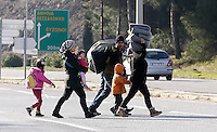 Pictured: A young family of migrants walk on the main road Tuesday 23 February 2016<br /> Re: Migrants trying to cross the Greek-FYRO Macedonian border, were turned away by the authorities in Idomeni, Greece.