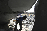 """A Palestinian boy play over debris at the site of a destroyed metal workshop targeted by an Israeli air strike in Gaza City, early 25 May 2007.""""photo by Fady Adwan"""""""