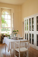 An ante-room off the dining room houses a glass-fronted display cabinet for dinner services and a white painted rustic table and chair for stacking plates before putting them away