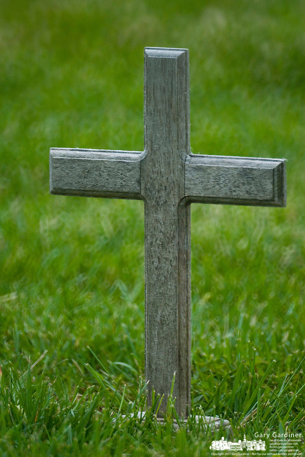 A wooden cross marks a veteran's grave marker in an Ohio cemetery.<br />