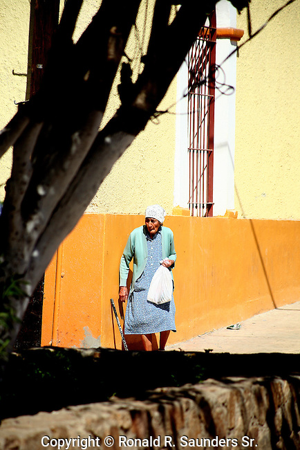 OLD WOMAN CARRIES BAG ON STREET IN MEXICO