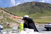 A Chinese Muslim man stop to eat yoghurt at the side of a road on the Tibetan Plateau, in western China.