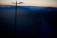 Electrical lines stand next to an oil field road stretching to the mountains west of Pendroy, Montana, USA.