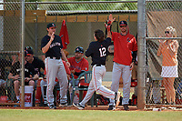 Ball State Cardinals left fielder Mack Murphy (12) high fives coach Dustin Glant and Ryan Peltier (7) during a game against the Saint Joseph's Hawks on March 9, 2019 at North Charlotte Regional Park in Port Charlotte, Florida.  Ball State defeated Saint Joseph's 7-5.  (Mike Janes/Four Seam Images)