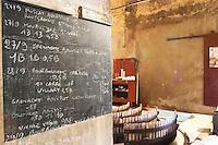 Notice board with journal. Chateau Mire l'Etang. La Clape. Languedoc. Concrete fermentation and storage vats. Sign on tank. France. Europe.