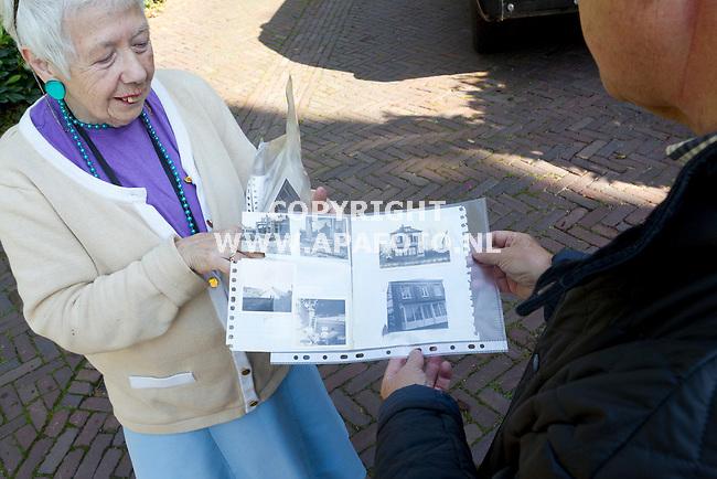 Oosterbeek, 200814<br /> Reportage Locaties Market Garden<br /> <br /> Foto: verteller Dhr Voskuil bij het huis aan de Annstraat 2 bij de kelder waar zijn moeder, in verwachting van hem, door een soldaat gered is van een granaat. De bewoonster laat foto's zien van het huis na de oorlog.<br /> Foto: Sjef prins - APA Foto