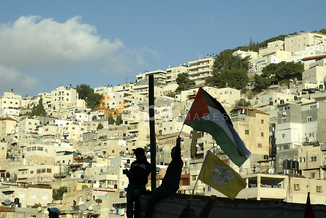The Palestinian flag is held up as Israeli, Palestinian and foreign activists hold a demonstration in the Arab east Jerusalem neighbourhood of Silwan against Jewish settlement activity in the Palestinian districts of the holy city on December 24, 2010. Photo by Mahfouz Abu Turk