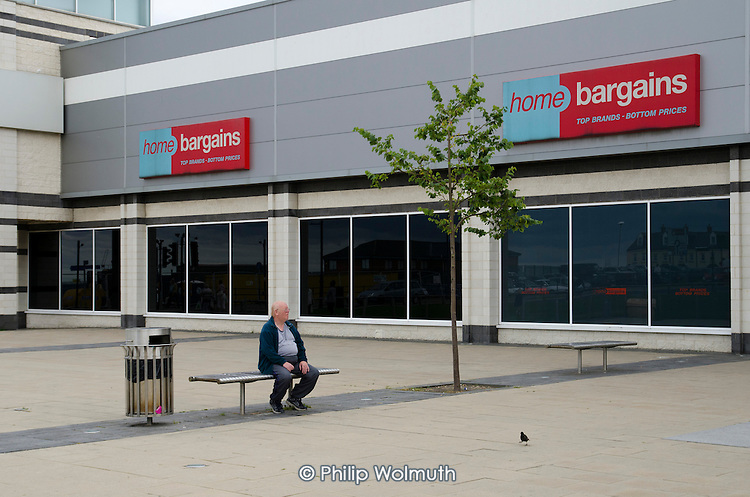 Elderly man in the new shopping precinct in Seaham, County Durham. Formerly known as Seaham Harbour, the town served as a port for the export of coal until the last local pit closed in 1992.  The harbour now functions at a much reduced level, importing coal from Eastern Europe and elsewhere.