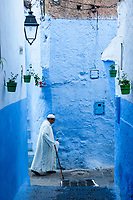Chefchaouen, Morocco.  Man Walking with a Cane in a Narrow Street.