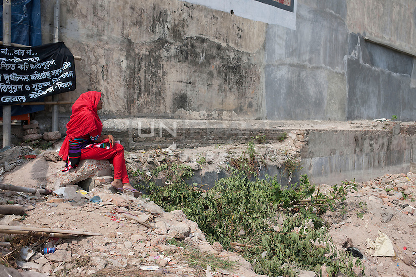 Relative of a victim killed in the collapse of Rana Plaza sits alone in front  of the collapse site in Savar, near Dhaka, Bangladesh