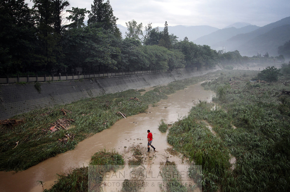 """A man crosses one of the main channels that makes up the Dujiangyan Irrigation System. The system is regarded as an """"ancient Chinese engineering marvel."""" By naturally channeling water from the Min River during times of flood, the irrigation system served to protect the local area from flooding and provide water to the Chengdu basin. Sichuan Province. 2010"""