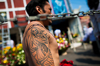 A Mexican devotee of Santa Muerte (Saint Death) shows his tattoo during a religious pilgrimage in Tepito, a violent neighborhood of Mexico City, Mexico, 1 May 2011. The religious cult of Santa Muerte is a syncretic fusion of Aztec death worship rituals and Catholic beliefs. Born in lower-class neighborhoods of Mexico City, it has always been closely associated with crime. In the past decades, original Santa Muerte's followers (such as prostitutes, pickpockets and street drug traffickers) have merged with thousands of ordinary Mexican Catholics. The Saint Death veneration, offering a spiritual way out of hardship in the modern society, has rapidly expanded. Although the Catholic Church considers the Santa Muerte's followers as devil worshippers, on the first day of every month, crowds of believers in Saint Death fill the streets of Tepito. Holding skeletal figurines of Holy Death clothed in a long robe, they pray for power healing, protection and favors and make petitions to 'La Santísima Muerte', who reputedly can make life-saving miracles.