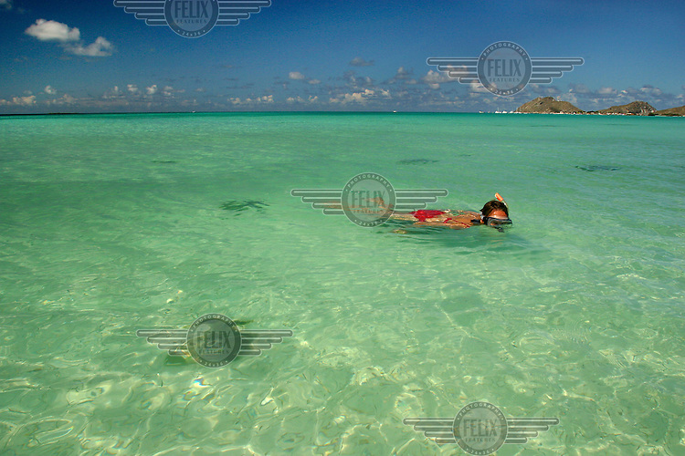 Tourist snorkeling in the clear waters off a beach on the Los Roques islands. Watersports such as snorkeling and diving are popular among tourists visiting the Los Roques National Park.